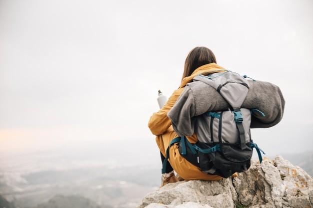Mulher com mochilão nas costas observando a natureza