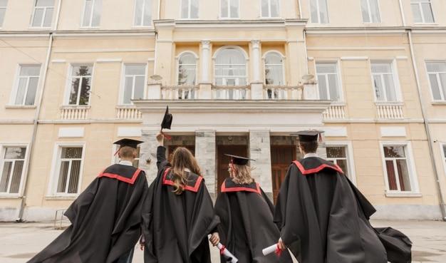 Alunos formados e comemorando em frente à faculdade
