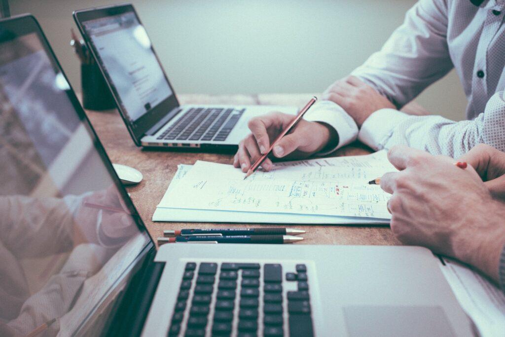 Pessoas trabalhando com 2 notebooks